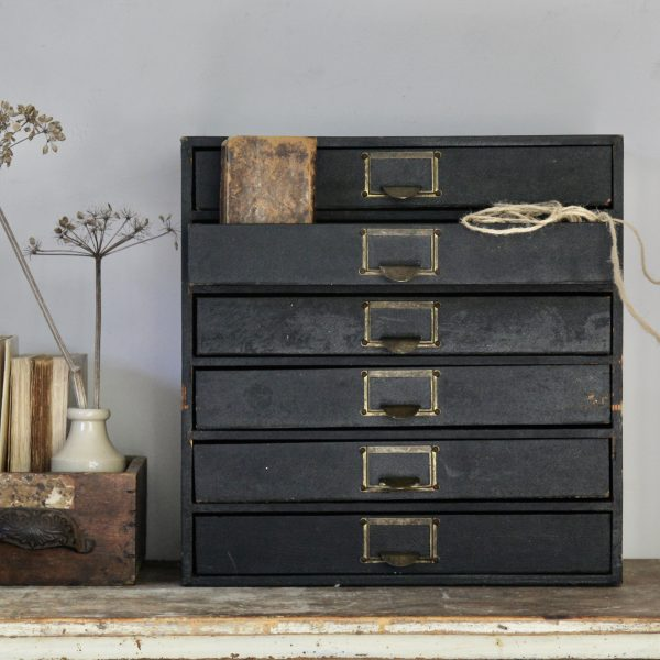 Attractive antique little bank of drawers from the 1950s covered in original black paper, each drawer with matching original brass handle. This piece benefits from six drawers.  There are some little imperfections to the back commensurate with age, but it is otherwise in good general vintage condition. Great little vintage set of drawers to store paper and other stationery items on a desk top, or as a beautiful set of drawers in the bedroom for make-up or jewellery.